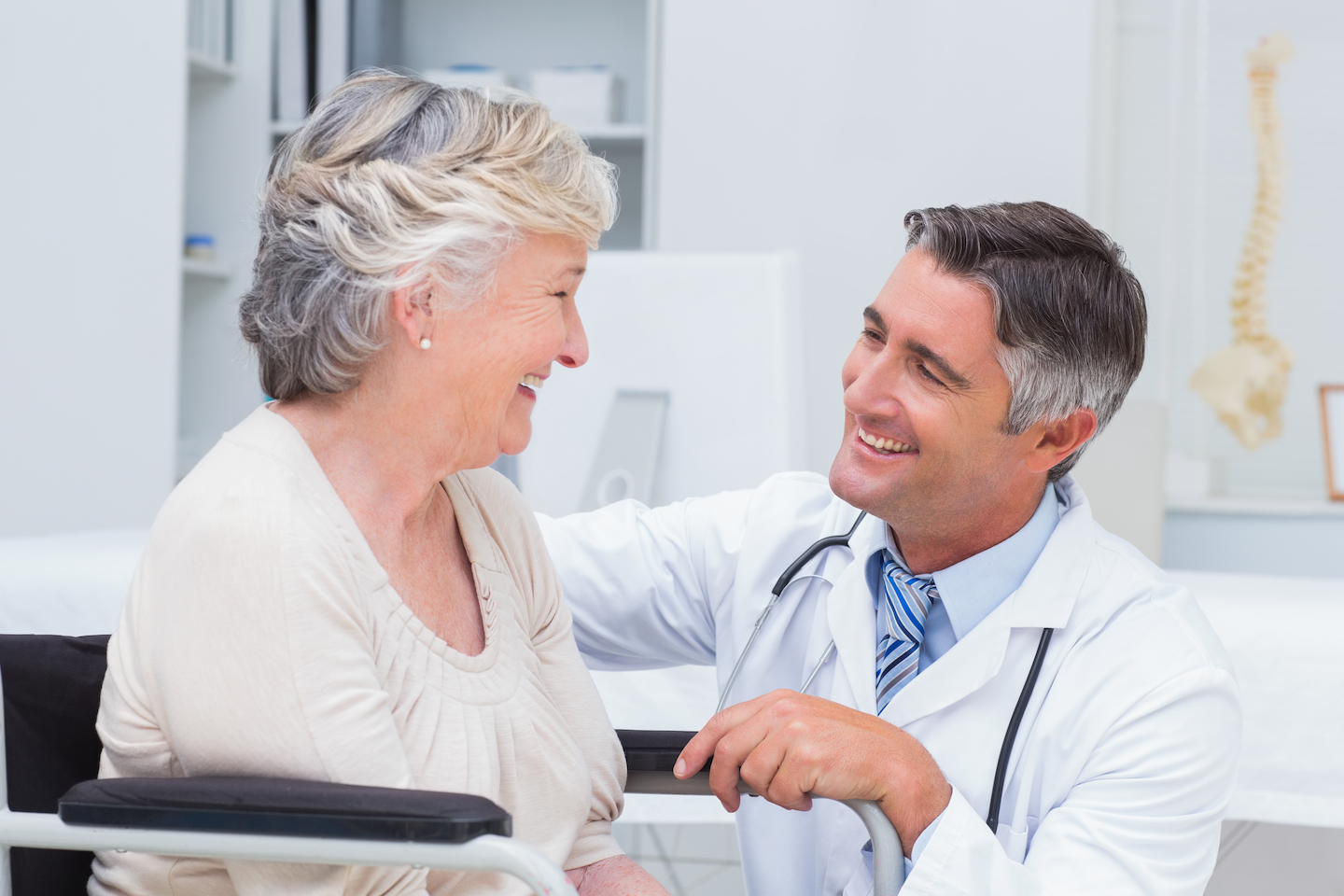 Happy doctor looking at patient in clinic